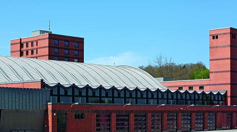 Wasser ist ihr Werkzeug: Das spiegelt sich auch im wellenförmigen Dach der Übungshalle der Staatlichen Feuerwehrschule bei Regensburg wider. Seit acht Jahren wird die ausgefallene Konstruktion aus den 1970er Jahren endlich lautlos und wirtschaftlich temperiert – durch Zehnder Deckenstrahlplatten. Bildquelle: Rheinzink, Ulm