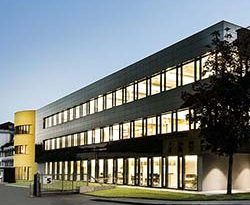 """Die Gestaltung und Erhaltung wertiger und nachhaltiger Gebäude ist seit vielen Jahren das Ziel der Sto SE & Co. KGaA. Prägnant zusammengefasst wird dieses Anliegen im Unternehmens-Motto """"Bewusst bauen"""". Diesem Anspruch wird der Baustoffhersteller aus dem Schwarzwald auch auf dem eigenen Firmengelände gerecht: Das neue Empfangs- und Bürogebäude wurde als Nullenergiehaus im Passivhausstandard erstellt und erhielt von der Deutschen Gesellschaft für Nachhaltiges Bauen (DGNB) das Gütesiegel in Platin. Im Foyer des neuen Gebäudes in der Sto-Firmenzentrale in Stühlingen überreichte die DGNB das Zertifikat an Gerd Stotmeister, Vorstand Technik der STO Management SE. """"Unser Ziel war es, nicht nur ein ästhetisches und energetisch optimiertes Gebäude zu bauen, sondern eines, das seine benötigte Energie selbst produzieren kann"""", betonte Stotmeister. """"Erreicht wird dies durch ein ausgeklügeltes Energiekonzept mit innovativer Technik."""" Dieses lobte auch die Parlamentarische Staatssekretärin im Bundesministerium für Umwelt, Naturschutz, Bau und Reaktorsicherheit, Rita Schwarzelühr-Sutter (SPD), die sich schon am Vortag ein Bild von dem Industriegebäude gemacht hatte. Ihr Fazit: """"Es zeigt uns: Nachhaltigkeit und ambitionierter energetischer Standard sind keine Vision, sondern heute schon Realität"""", so die Politikerin, die das Engagement des Baustoffherstellers auf diesem Gebiet würdigte: """"Klimaschutz braucht Vorbilder."""" Schon während der Planungsphase war das Gebäude mit dem Vorzertifikat in Gold, der damals höchstmöglichen Auszeichnung, bedacht worden. Nach zweijähriger Bauphase erreichte es den Platin-Standard – die höchste Auszeichnung, die bislang erst wenigen Bürogebäuden in Deutschland verliehen wurde. Damit würdigt die DGNB die Nachhaltigkeit des Gebäudes über seinen gesamten Lebenszyklus. Bei der Bewertung werden die Themenfelder Ökologie, Ökonomie, soziokulturelle und funktionale Qualität, Technik sowie Planungs- und Bauprozess bewertet. Zudem fließen die Standortqualität,"""
