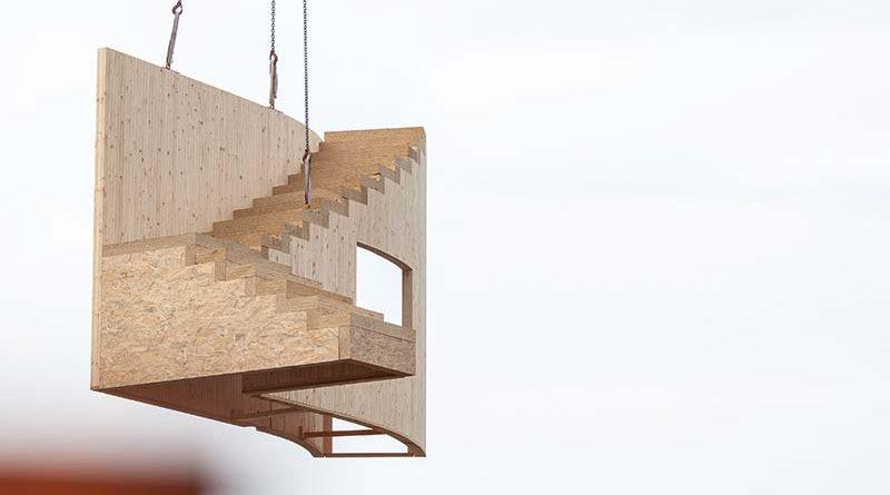 Vorgefertigtes Treppenelement wird mit dem Kran an die richtige Stelle positioniert und fachmännisch montiert. Bildnachweis: SWISS KRONO │ Foto: tm studios